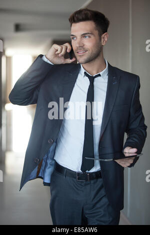 Businessman taking phone call on the move - Stock Photo
