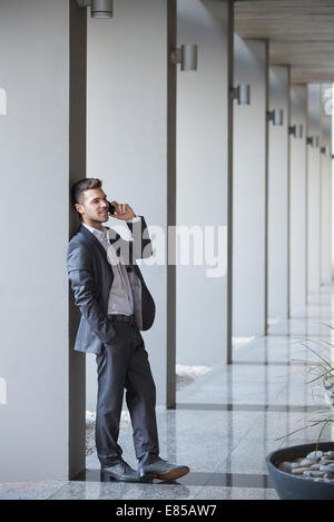 Young executive taking phone call while leaning against column in building lobby - Stock Photo