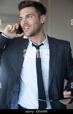Young businessman taking phone call on the move - Stock Photo
