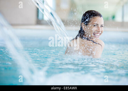 Woman relaxing under fountain in swimming pool - Stock Photo