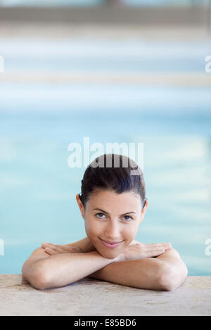 Woman relaxing in swimming pool, portrait - Stock Photo