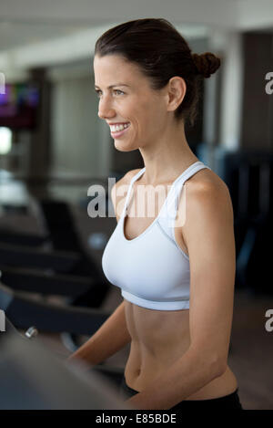 Woman exercising on treadmill in health club - Stock Photo