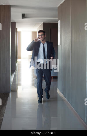 Young businessman talking on phone while walking through office - Stock Photo
