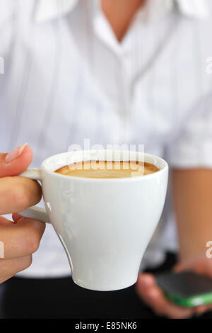 Female holding a cup of coffee - Stock Photo