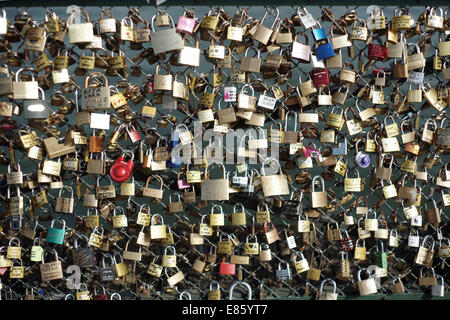 Padlocks on chain link fence on a bridge in Paris, attached by lovers to symbolise their everlasting love - Stock Photo