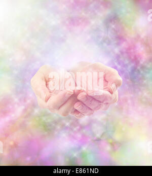 Cupped healing hands emerging from misty rainbow colored sparkling soft energy background - Stock Photo