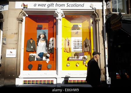Old man walking past a shop window display on the Royal Mile, Edinburgh Old Town - Stock Photo