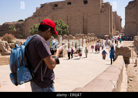 Egypt, Luxor, Karnak Temple, tourist photographing Avenue of Rams at temple entrance - Stock Photo