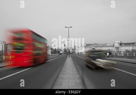 London Red Bus and a Black Cab on a road in London blurred by motion - Stock Photo