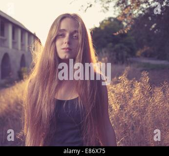 Confident young blond women against gold sunset light. Autumn time. Backlit. She looks like as very relaxed and thinking deep. Cute romantic girl, attractive blond woman enjoying autumn yellow sunlight.