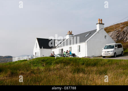 People sitting outside the Skoon Art Cafe at Geocrab on South Harris in the Outer Hebrides. - Stock Photo