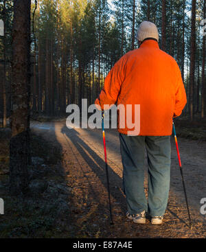 Elderly woman standing in the forest with nordic walking poles , Finland - Stock Photo