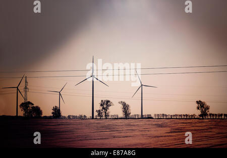 Retro dark abstract picture of wind turbines on field. - Stock Photo