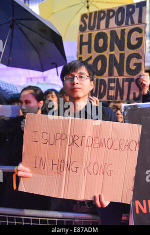 Portland Place, London, UK. 1st October 2014. Protesters hold banners and umbrellas opposite the Chinese Embassy - Stock Photo