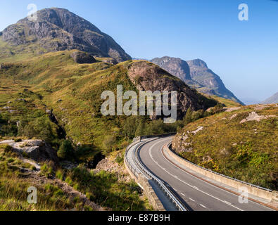 The new section of road passing through Glencoe at the meeting of the waters with the Three Sisters in background - Stock Photo