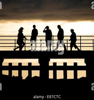 5 five People walking  in silhouette, walking on  jetty pier deck on a summer evening Aberystwyth Wales UK - Stock Photo