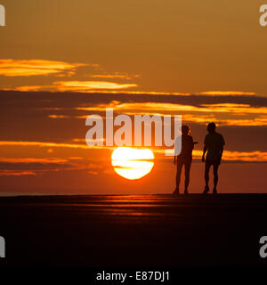 Two young People in silhouette, walking on  jetty pier on a hot warm summer evening at sunset Aberystwyth Wales - Stock Photo