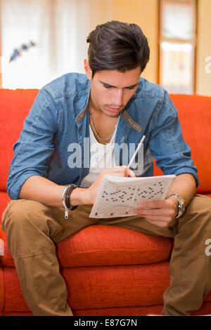 Young man sitting doing a crossword puzzle looking thoughtfully at a magazine with his pencil in one hand as he - Stock Photo
