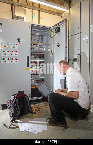 A building services engineer monitors the electrical control cabinet in the plant room of a large office block using - Stock Photo