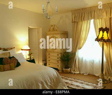 White Voile And Yellow Silk Curtains On Window In Pale Yellow Bedroom With  Lighted Standard Lamp