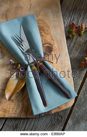Tied napkin and silverware on wooden cutting board - Stock Photo