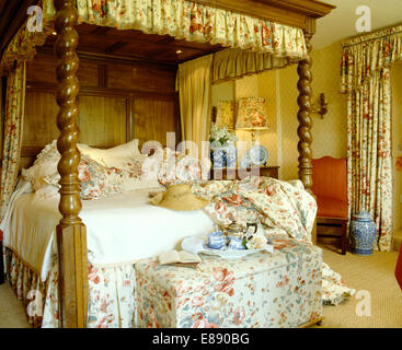 Floral drapes on four poster bed in country bedroom with teaset on floral ottoman at the foot of the bed - Stock Photo
