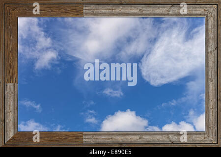Old wood window with blue sky and clouds. - Stock Photo