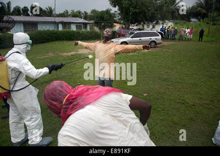 Members of the Ebola body removal team spray each other with chlroine to disenfect themselves after removing a body - Stock Photo