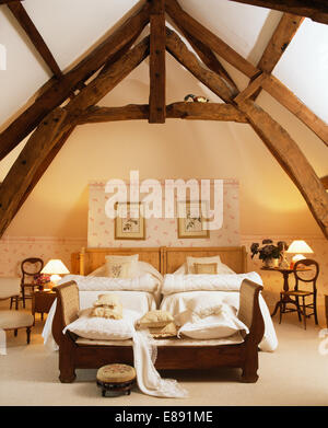 High, beamed apex ceiling in French country bedroom with sofa at the foot of twin beds with white quilts - Stock Photo