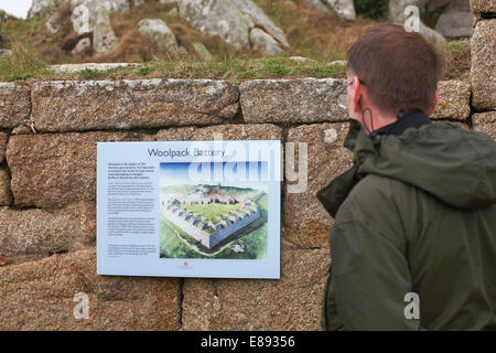 Man reading Woolpack Battery information sign on Garrison Walls at Hugh Town, St Marys, Isles of Scilly, Scillies, - Stock Photo