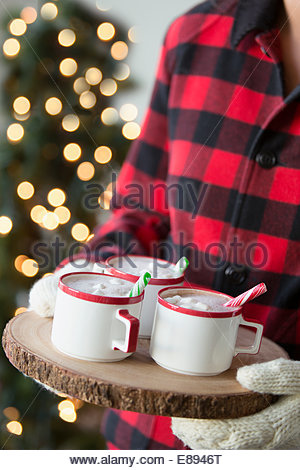 Woman carrying hot cocoa on wood tray - Stock Photo