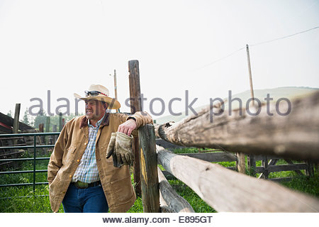 Rancher leaning on pasture fence - Stock Photo