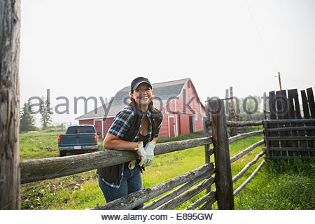 Smiling rancher leaning on pasture fence - Stock Photo
