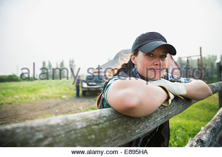 Portrait of confident rancher leaning on fence post - Stock Photo