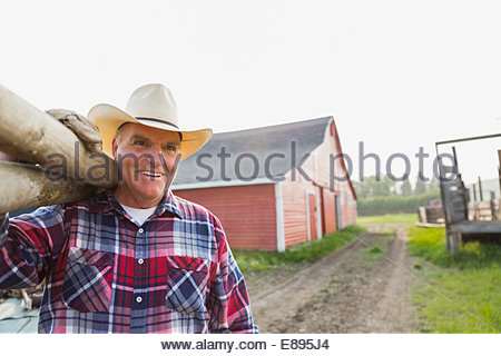 Smiling rancher carrying fence posts outside barn - Stock Photo