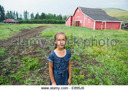 Portrait of girl in rural pasture outside barn - Stock Photo