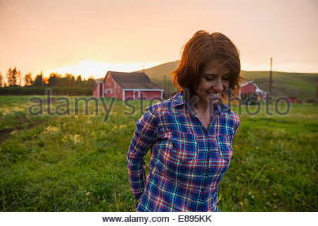 Woman walking in rural field at sunset - Stock Photo