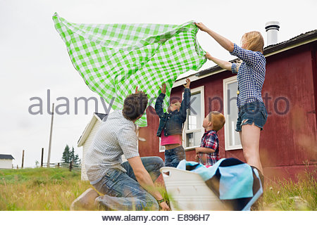 Family with picnic blanket in rural field - Stock Photo