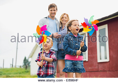 Parents watching children play with pinwheels - Stock Photo