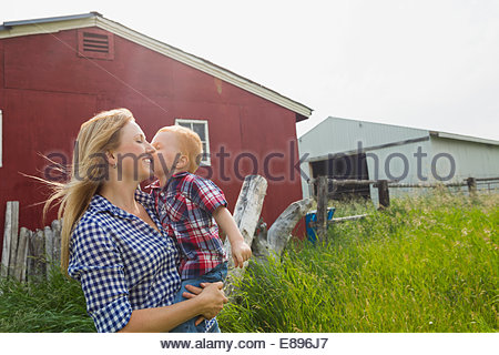 Little boy kissing mother on cheek, outdoors by barn - Stock Photo