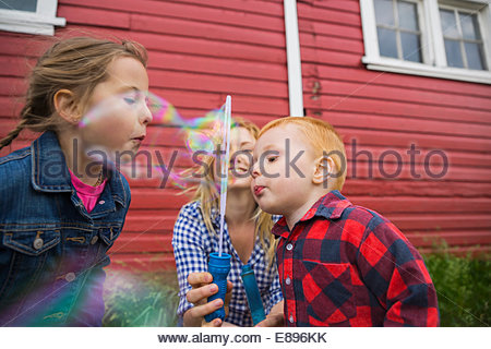 Brother and sister blowing bubbles - Stock Photo