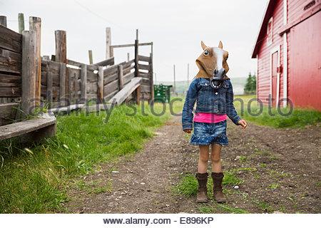 Girl wearing horse mask outside barn - Stock Photo