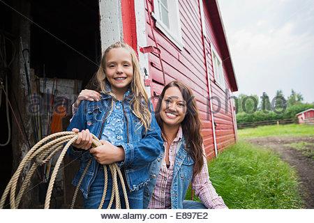 Portrait of mother and daughter in barn doorway - Stock Photo