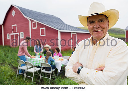 Portrait of rancher at family dinner outside barn - Stock Photo