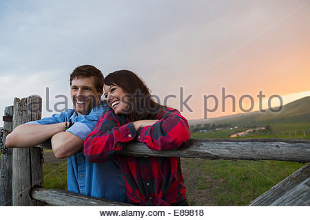 Couple leaning on rural fence post at sunset - Stock Photo