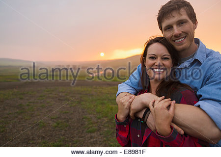 Portrait of couple hugging in field at sunset - Stock Photo
