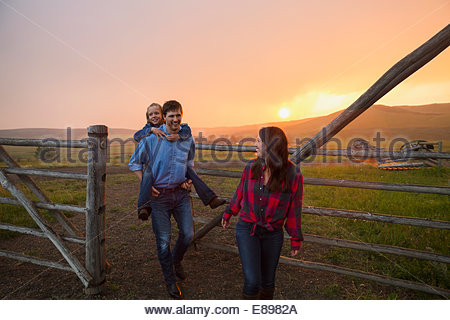 Family walking through pasture gate at sunset - Stock Photo