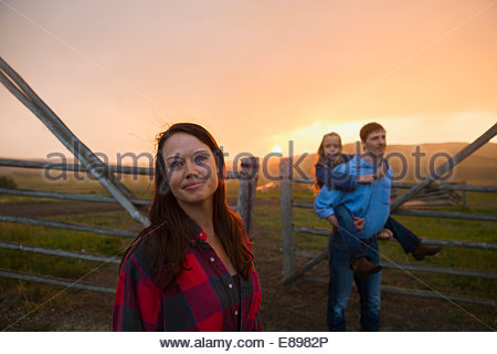 Woman with family in pasture at sunset - Stock Photo