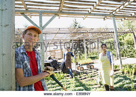 Portrait of confident workers tending to plants - Stock Photo