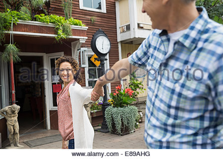 Smiling couple holding hands outside cafe - Stock Photo